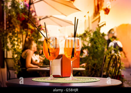 Aperol Spritz Cocktail. Alcoholic beverage based on table with ice cubes and oranges. - Stock Photo