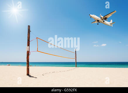 Volleyball net on the beach and plane with tropical sea and over light the sun - Stock Photo