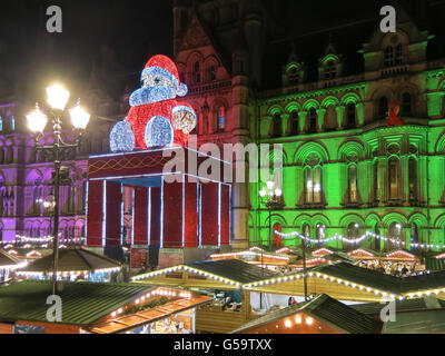 Christmas market and Big Santa Claus sitting on town hall on Albert Square at night, Manchester, England, United - Stock Photo