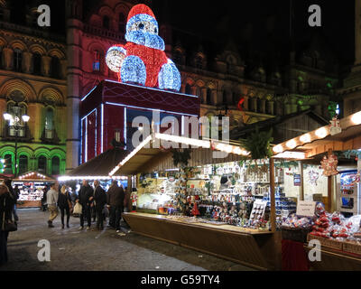 People shopping on Christmas market and town hall with Big Santa on Albert Square at night, Manchester, England, - Stock Photo