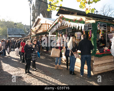 People shopping at market stalls of Christmas Market on Albert Square in Manchester, England, United Kingdom - Stock Photo