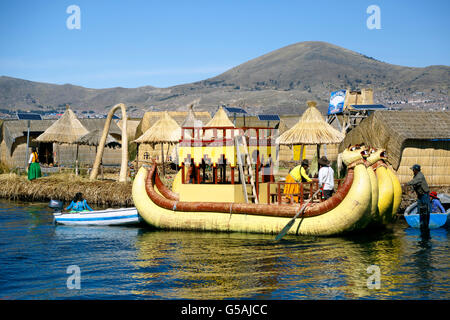 Yellow totora reed boat and houses on totora reed island, Uros Islands, Lake Titicaca, Puno, Peru - Stock Photo