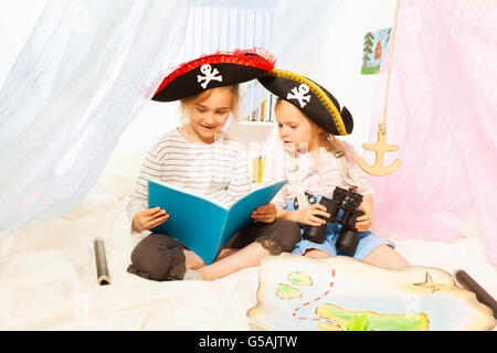 Two girls in pirate's costumes reading fairy-tale - Stock Photo