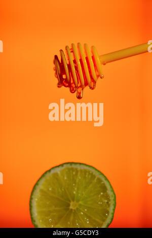Honey flowing on lemon over yellow background - Stock Photo