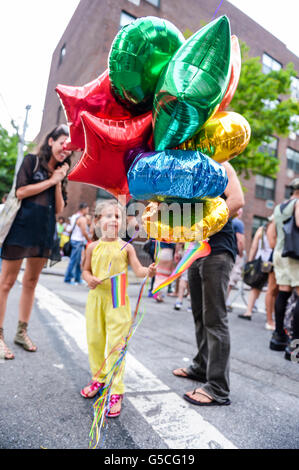 NEW YORK CITY - JUNE 30, 2013: A child holds a rainbow flag and a bouquet of colorful balloons at the annual gay - Stock Photo