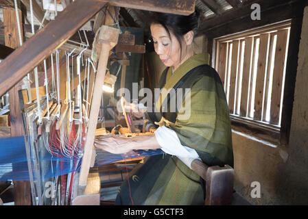 Traditional weaving on a loom at Ryukyu Mura, Okinawa, Japan - Stock Photo