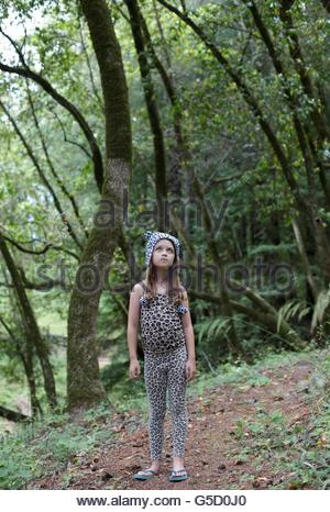 A young girl alone in the woods, looking up, wearing animal patterned clothing and hat. - Stock Photo