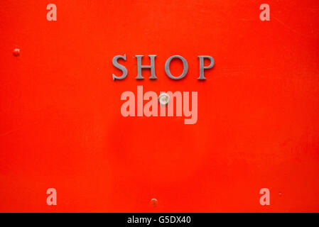 Shop written in metal letters on a bright red door background - Stock Photo