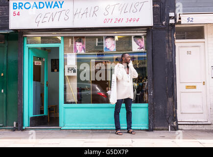 Hipster afro man on the phone outside a gents hair stylist in the cool hipster area Broadway Market, East London - Stock Photo
