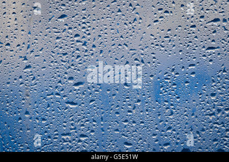 Water drops on a window pane in front of blue background - Stock Photo