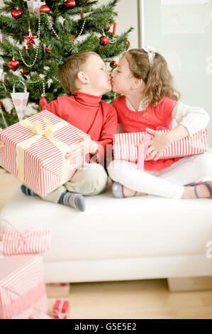 Brother and sister with Christmas present kissing - Stock Photo