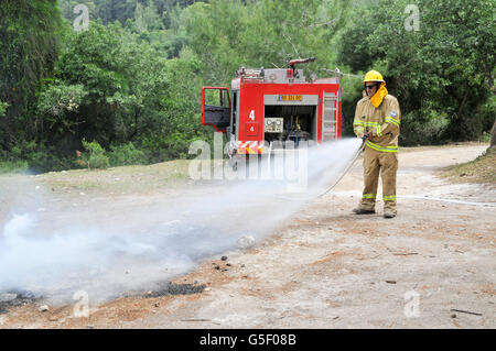 Fireman in protective clothing extinguishes a fire as part of a fire fighting drill - Stock Photo