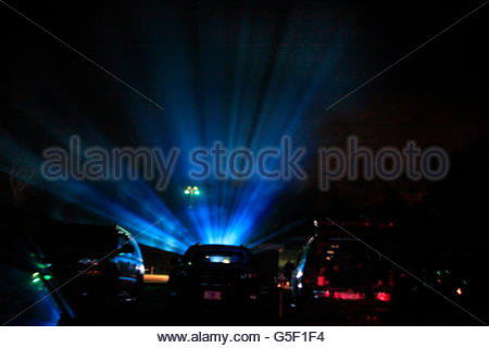 Projector light beams at drive in movie theater - Stock Photo