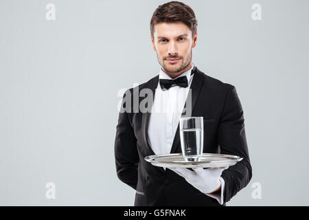 Portrait of waiter in tuxedo and gloves holding glass of water on metal tray - Stock Photo