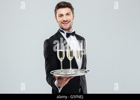 Cheerful young butler in tuxedo smiling and offering champagne - Stock Photo