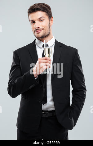 Portrait of attractive young businessman in suit and tie with glass of champagne over white background - Stock Photo