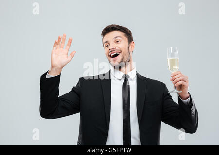 Happy excited young businessman holding glass of champagne and celebrating over white background - Stock Photo