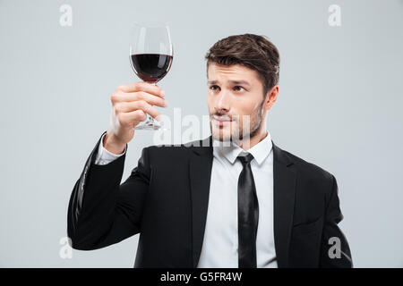 Serious young man sommelier in suite tasting red wine in glass over white background - Stock Photo