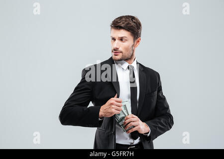 Serious young businessman in suit and tie hiding money in pocket over white background - Stock Photo
