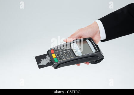 Hand of businessman in suit holding bank terminal with credit card over white background - Stock Photo