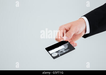 Hand of businessman in suit holding credit card over white background - Stock Photo