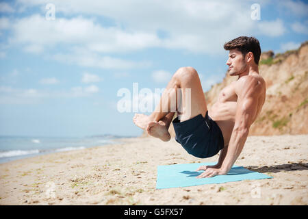 Man with eyes closed balancing on his hands and practicing yoga on the beach - Stock Photo
