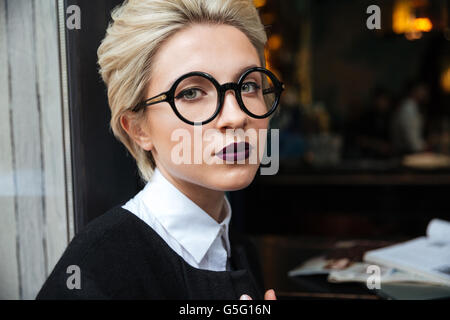 Close-up portrait of a beautiful girl wearing glasses and sitting in cafe - Stock Photo