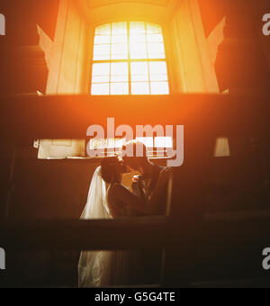 bride and groom on the background of a window. - Stock Photo