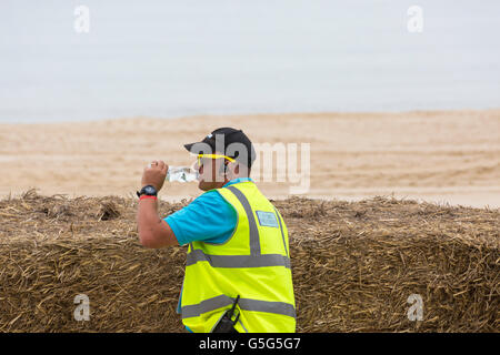 Marshall wearing hi vis vest and drinking bottle of water at Bournemouth Wheels Festival in June - Stock Photo