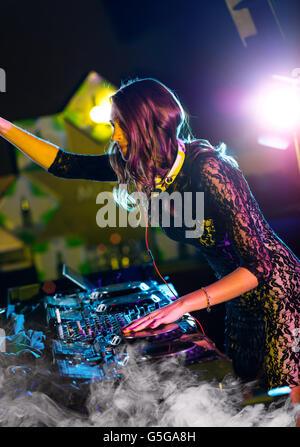 Disc jockey brunette girl mixing electronic music in club - Stock Photo
