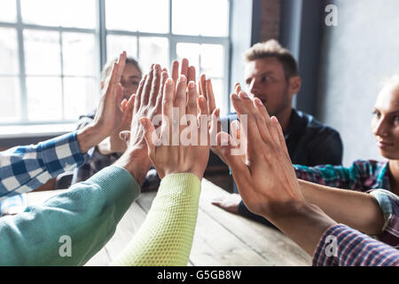Modern business meeting concept, people on casual clothes sitting around wooden table and give high five - Stock Photo