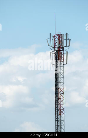 Top part of cell phone communication tower with multiple antennas and solar panels that supply of electricity against - Stock Photo