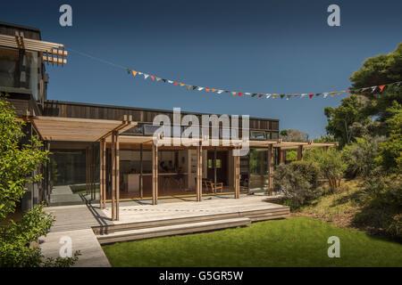 Shot of house from garden with blue sky and bunting. PEKA PEKA II HOUSE, Peka Peka - Kapiti Coast, New Zealand. - Stock Photo