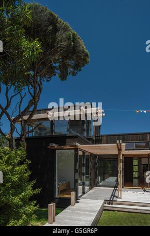 Shot of house from garden with blue sky and endemic tree. PEKA PEKA II HOUSE, Peka Peka - Kapiti Coast, New Zealand. - Stock Photo