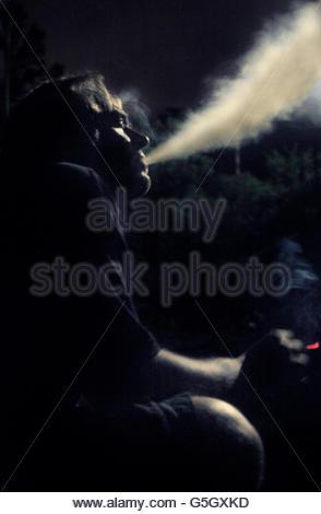 Candid profile photograph of man smoking - Stock Photo