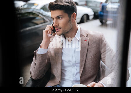 Attractive young businessman sitting and talking on mobile phone sitting outdoors in cafe - Stock Photo