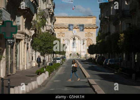 Local lady crosses Rue Foch in front of the 17th century Arc de Triomphe in Montpellier, south of France. - Stock Photo