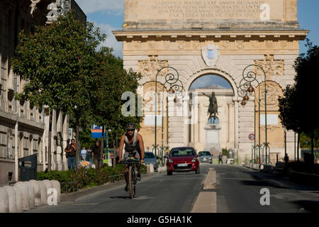Local cyclist on the Rue Foch in front of the 17th century Arc de Triomphe in Montpellier, south of France. - Stock Photo