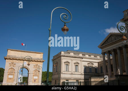 Arc de Triomphe with Romanesque architecture of the Palais de Justice and retro street lighting in Montpellier, - Stock Photo
