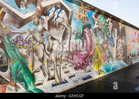 Sections of the Berlin Wall, now covered in street art at the East Side Gallery in Berlin, Germany - Stock Photo