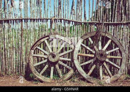 Two Old Wagon Wheels Near The Wooden Fence. Old Cart Wheel As Symbol And  Concept
