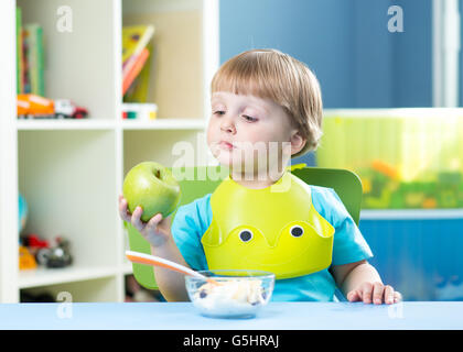 child eating apple at dinner in nursery at home - Stock Photo