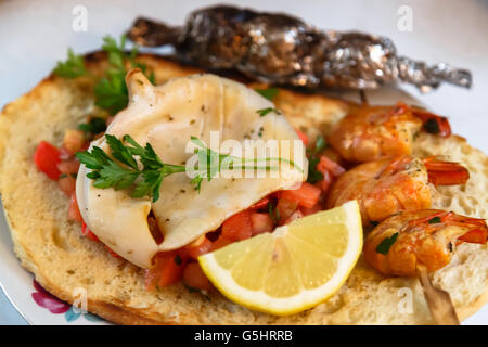 Grilled calamary and shrimps on Italian bruschetta - Stock Photo