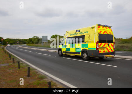 Emergency NHS Ambulance responding to incident on the Coastal Road of the resort, in Southport, Merseyside, UK - Stock Photo