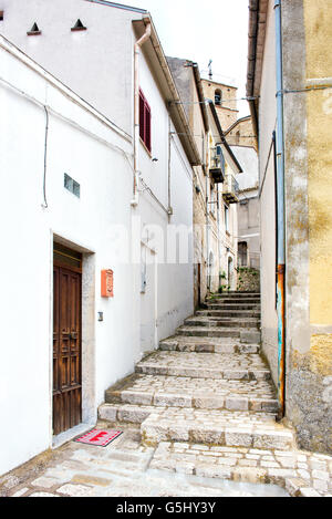 Narrow old cobbled street with steps leading up the hill between buildings in a village, view from the bottom looking - Stock Photo