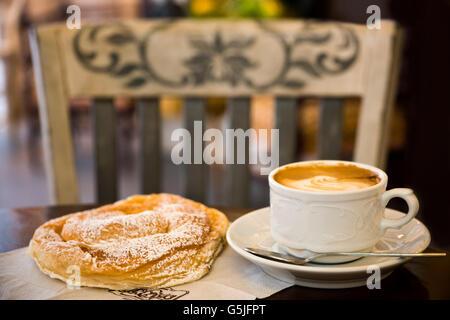 Horizontal close up of a cup of coffee and traditional ensaimada or ensaïmada at a cafe, Majorca. - Stock Photo
