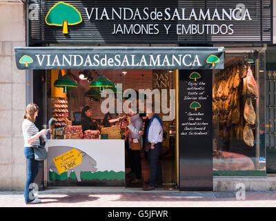 Horizontal view of customers at a traditional Iberian ham delicatessen in Palma, Majorca. - Stock Photo