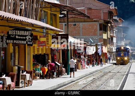 Train going by shops and restaurants, Machu Picchu Pueblo (fka Aguas Calientes), Cusco, Peru - Stock Photo