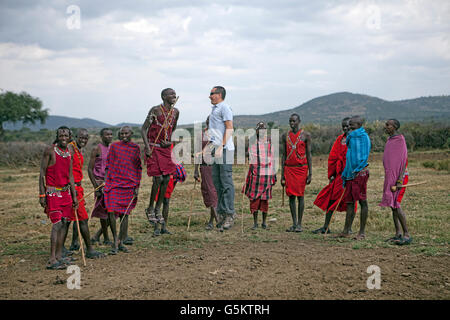 Group of Maasai warriors and one tourist doing a ceremonial dance in a Maasai village, Kenya, Africa. - Stock Photo