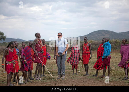 Group of Masai warriors and one tourist doing a ceremonial dance in a Maaai village, Kenya, Africa. - Stock Photo